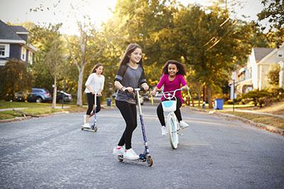 Niños andar en bicicleta y andar en scooter en la calle.